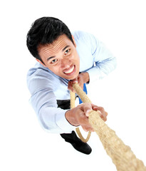 Young businessman climbing up by using a rope