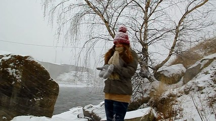 Young girl walking in winter snow falls