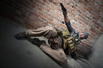 Soldier aiming pistol on bricks background