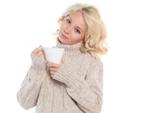 Young woman in a warm sweater and a mug in his hands