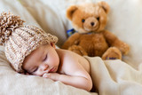 Little baby boy sleeping with teddy bear