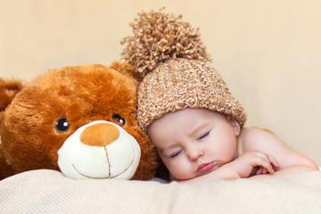 Little baby boy sleeping with teddy bear