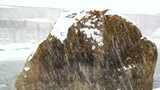 Snow falls against the backdrop of a huge flying stone, snow
