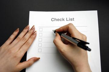 チェックリストと女性の手