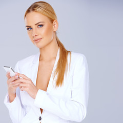 Beautiful stylish blond in white using a mobile