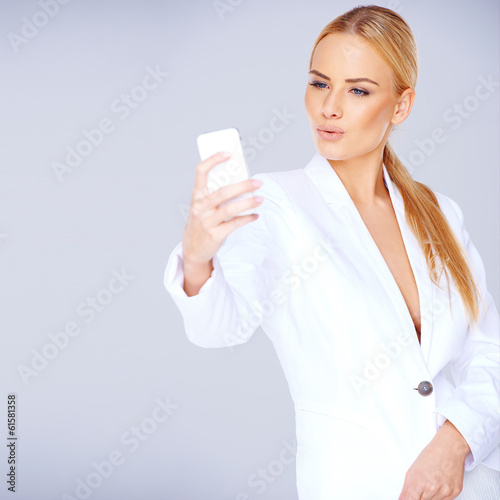 Elegant blond in a sexy suit texting on her mobile