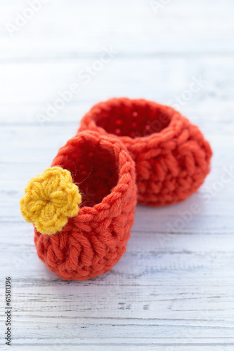 Orange crocheted baby shoes with flower