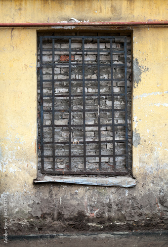 Old yellow building facade with locked window