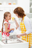 Little girl and mother having fun washing the dishes