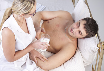 Woman caring man with milk