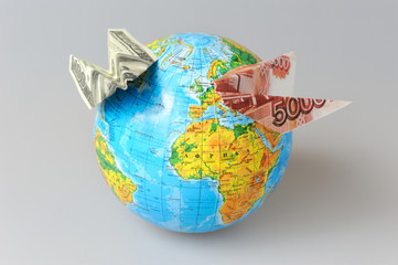 Globe with origami planes made from money on gray