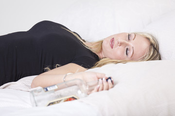 Drunk woman in bed with bottle