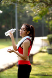 Slim young woman drinking water after exercises
