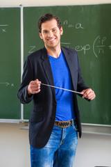 Lehrer mit Zeigestock im Klassenzimmer einer Schule