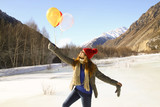 Happy girl with balloons on the ice against the background of sn