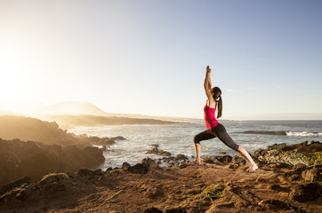 Young woman practicing yoga warrior pose near the ocean at sunse