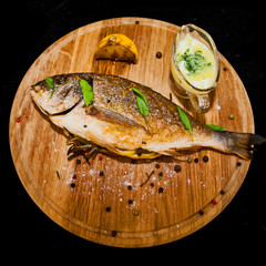 Grilled fish with lemon and spices on a wooden board
