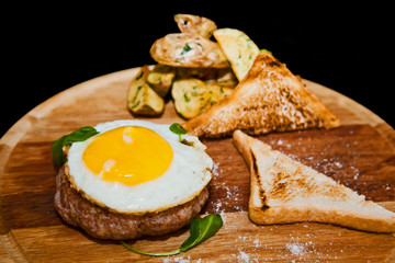 Scrambled eggs on meat with fried potatoes and toast