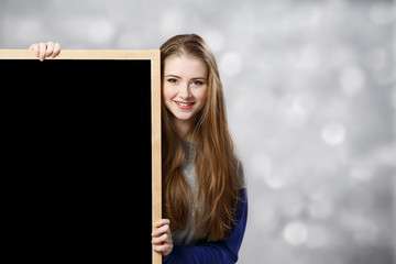 student female holding a chalkboard at light background