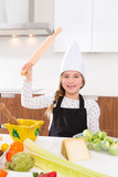 kid girl chef on countertop funny gesture with roller knead