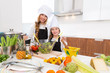 Kid girls junior chef friends hug together in countertop
