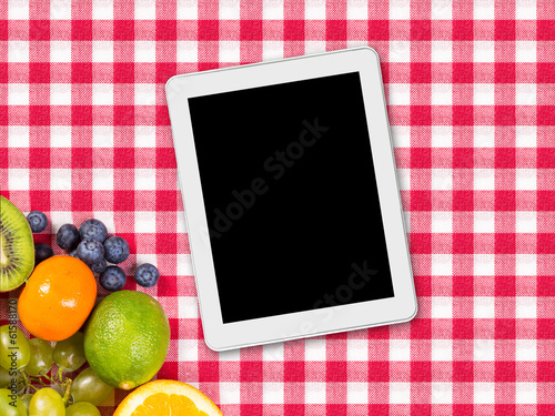 tablet and fruit on tablecloth textile