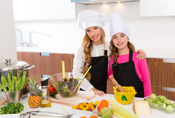 Kid girls junior chef friends hug together at cooking school