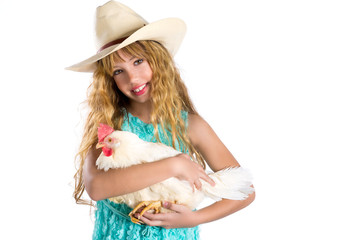 Blond kid girl farmer holding white hen on arms