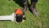Gardener man in gumboots hand start gass trimmer cutter