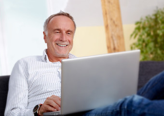 Mature man with laptop at home