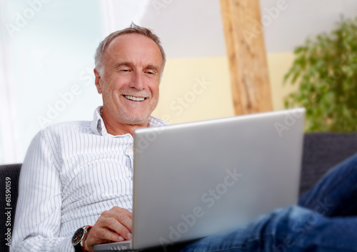 canvas print picture Mature man with laptop at home