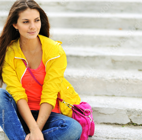 Stylish beautiful teen girl sitting on a stairs in colorful clot