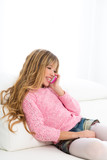Blond kid girl playing fun talking to mobile phone on sofa