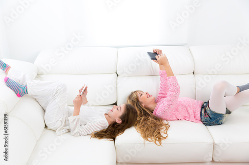 kid girls having fun playing with tablet pc lying sofa