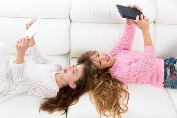 kid girls having fun playing with tablet pc lying sofa