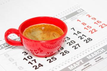 Чашка кофе на фоне календаря