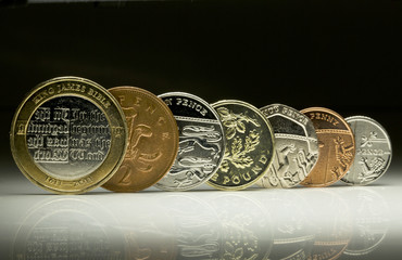 UK Currency coins balanced in a row on white