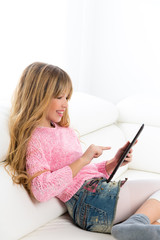 Blond kid girl playing with tablet pc on white sofa