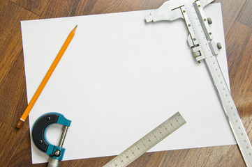 measuring instruments, pencil and white sheet of paper