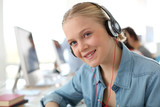 Blond student girl in computing class with headphones on