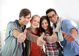 Group of cheerful students showing thumbs up