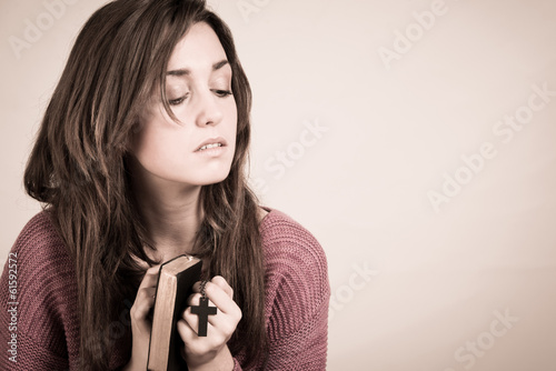 Young woman holding the bible and a cross