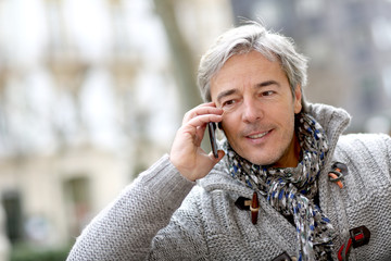 Portrait of mature man talking on phone in street