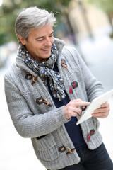 Man in city street using digital tablet