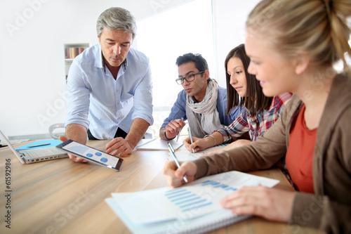 Leinwanddruck Bild Business school students in marketing class with teacher
