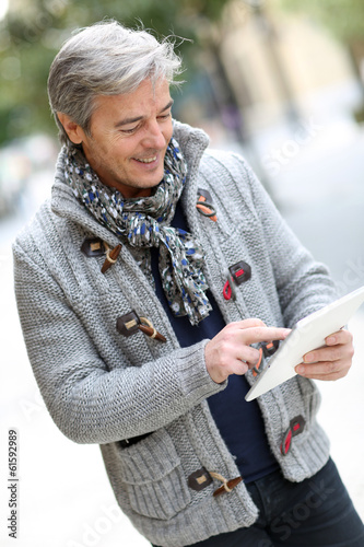 Man in city street using digital tablet