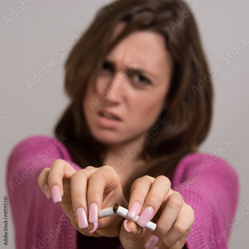 Out of focus image of young woman breaking cigarette