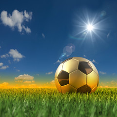 Goldener Fussball vor brasilinisch farbener Umgebung