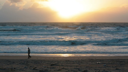 Man walking on the beach with storm waves at sunset