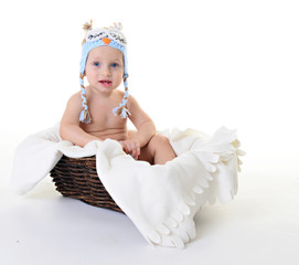 Beautiful baby in a cap owl sitting in a basket